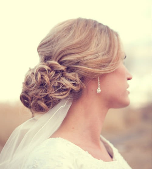These beautiful loose airy curls provide a soft romantic look. This look is best for fine hair. If your hair is too thick and heavy, you will loose the airy look. This style can work on any face shape as long as you keep some curls around the face to soften it according to latest-hairstyles.com. (Photo by Lindsey Shaun Photography)