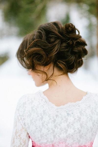 This updo provides some volume. Leave a few strands down around the face for a soft, elegant look. This full-bodied style looks great on brunettes but any color hair would look amazing with this style. (Photo Credit: Ciara Richardson Photography)